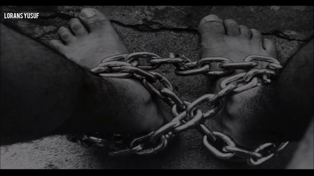 Zwei Füße, gefesselt mit einer Kette, oben links das Logo des Kanals