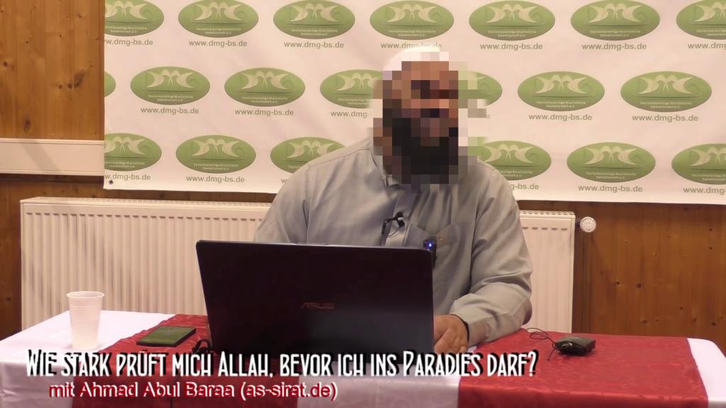 Bild aus dem Video. DMG e.V. Hintergrund mit Logo, im Vordergrund Mann mit Laptop an weißem Tisch mit roter Tischdecke
