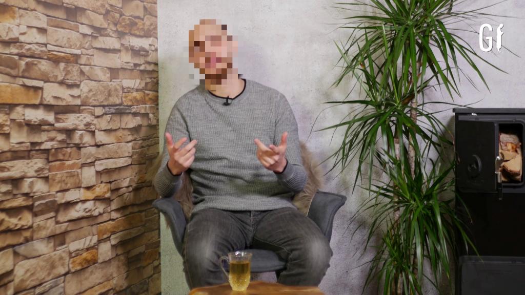 Ein Mann, sitzend, zwischen Mauertapete und Zimmerpflanze